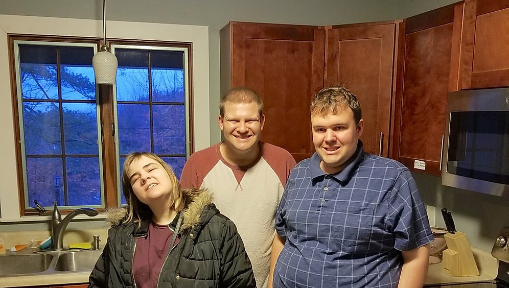 Image of Alexandra, Brian, and Travis posing in the kitchen of the group home.