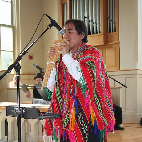 Picture of Etienne Perley, wearing his multi-colored poncho, performing with his panpipes at church.