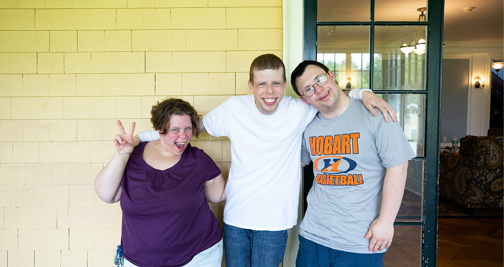 Image of students Carly, Tim, and Ben posing together for the camera against the yellow wall of BHMA's back porch.