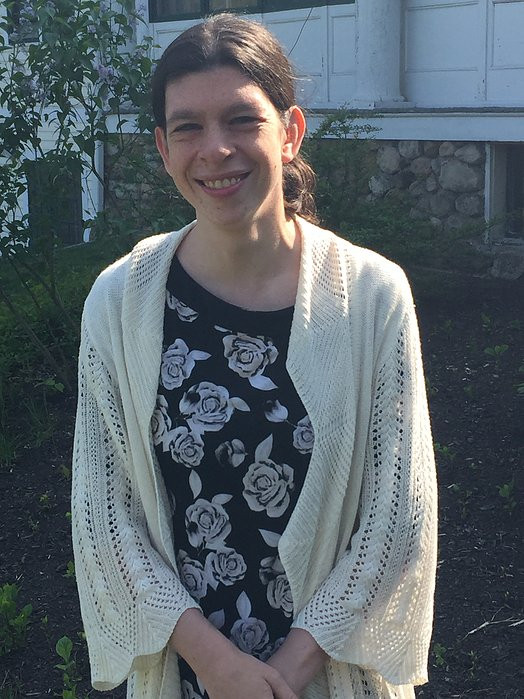 Image of Tori Ackley, wearing a black dress white white patterns over an off-white sweater, posing in BHMA's backyard.