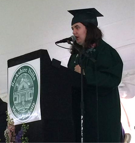 Image of Carly, wearing her green graduation cap and gown, speaking at the on-stage podium.