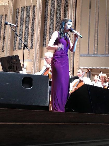 Image of Tori, wearing a floor-length purple dress, singing on stage at the Cleveland Pops Orchestra.