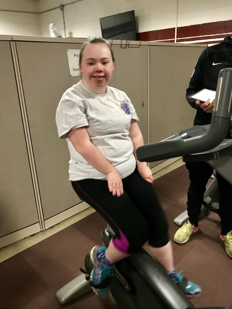 Image of Jen Barrett, wearing a gray t-shirt and black leggings, sitting atop an exercise bike at the UMass Body Shop.