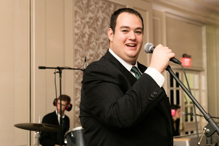 Image of Jeremy Swartz, wearing a black suite and white dress shirt, holding a microphone as he sings at a BHMA event.