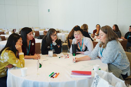 Female presenting people gather around a table at Stratagem 2019