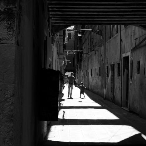 Man and child walking down a street.jpg