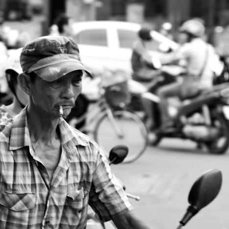 Man smoking while riding his moped.jpg