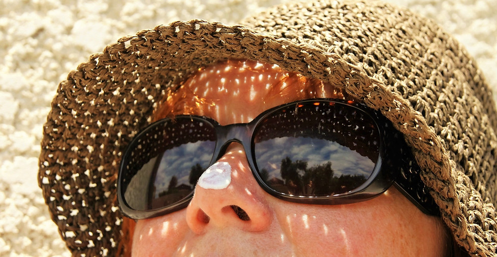 woman wearing hat, sunglasses and sunscreen
