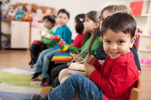 Little boy and preschool children playing instruments in music class