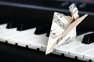 Paper airplane made of sheet music resting on piano keys