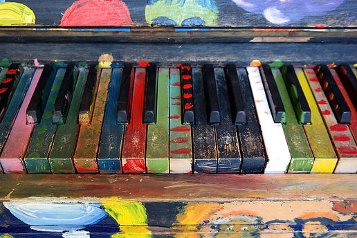 Old piano painted with multi-colored patterns and designs