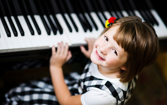 Young girl with flowers in her hair playing piano and looking up at the camera