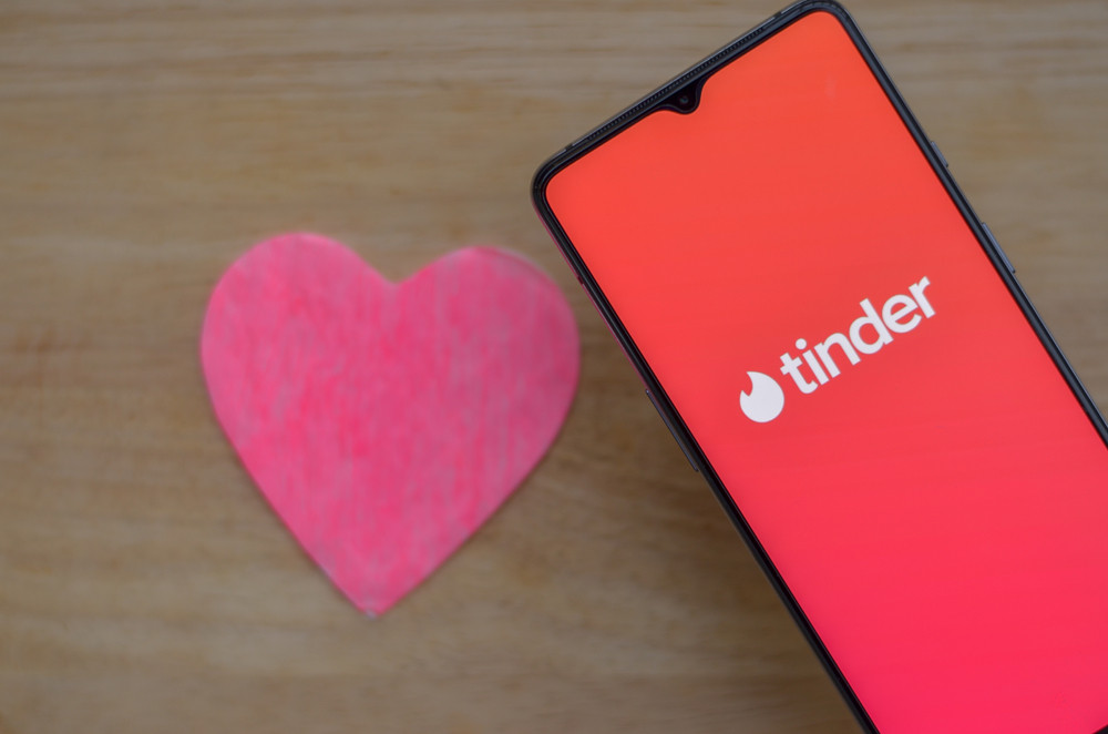 Flat lay with Tinder app logo on a smartphone screen with a pink heart on a wooden background on display