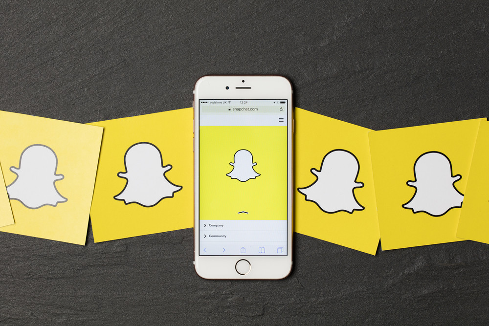 An apple iPhone showing the snapchat application alongside other snapchat logos.