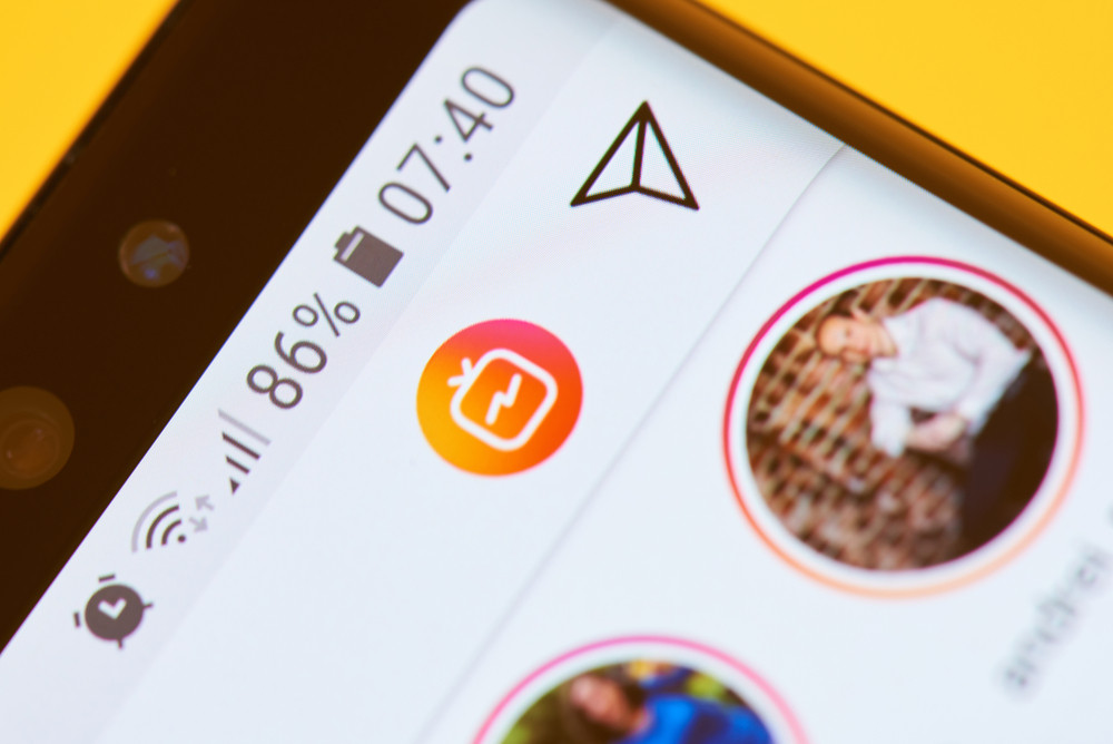 Sending in instagram direct message icon on smartphone screen macro view