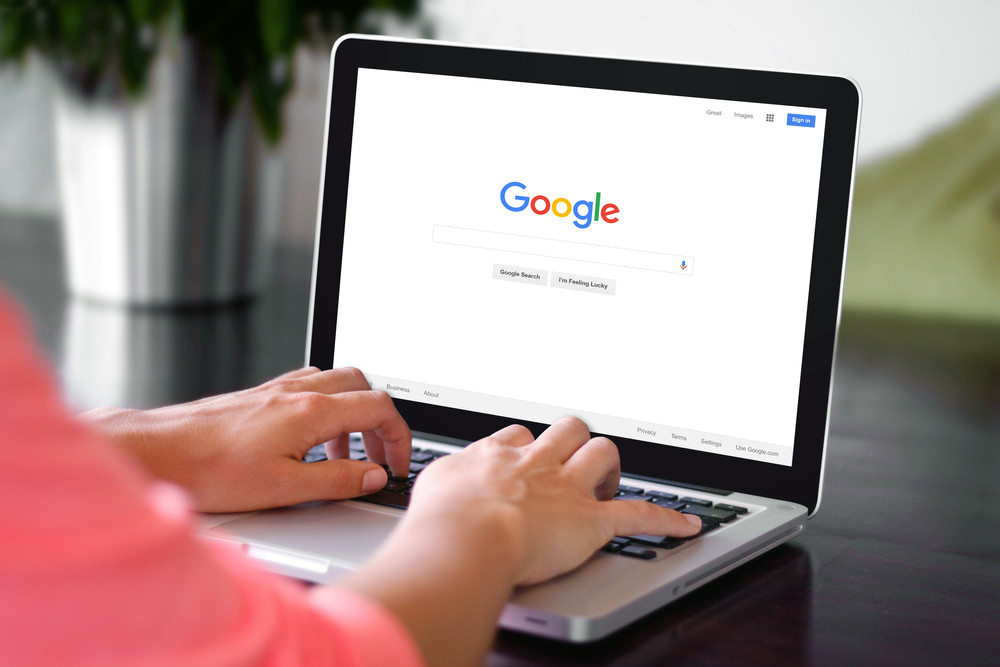 A woman is typing on Google search engine from a laptop.
