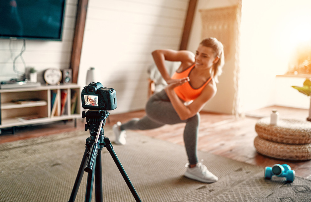 Athletic woman blogger in sportswear shoots video on camera as she does exercises at home in the living room