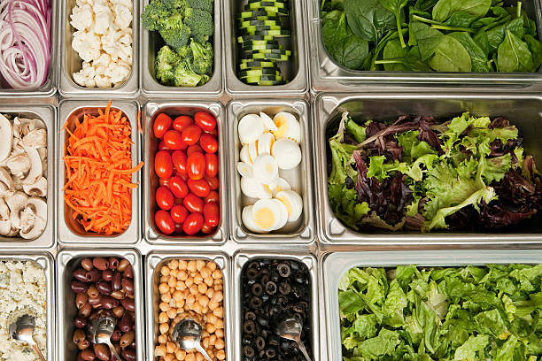A display of different bin of vegetables and legumes for a salad.