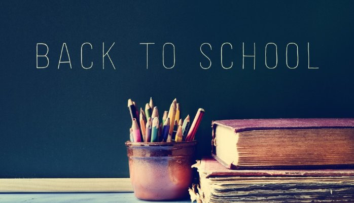 """""""Back to School"""" sign with a jar of pencils/pens and a book."""