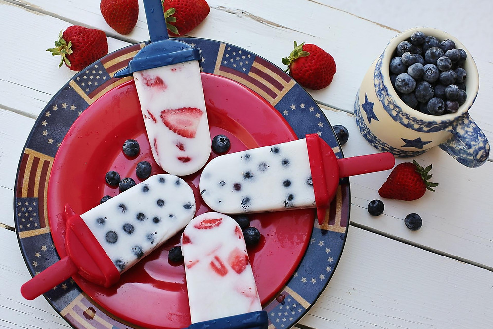 Fruit popsicles with strawberries and blueberries on an American plate.