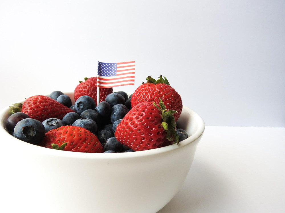 Strawberries and blueberries with a small American flag.