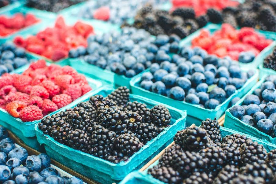 Blackberries, raspberries, blueberries in carts.