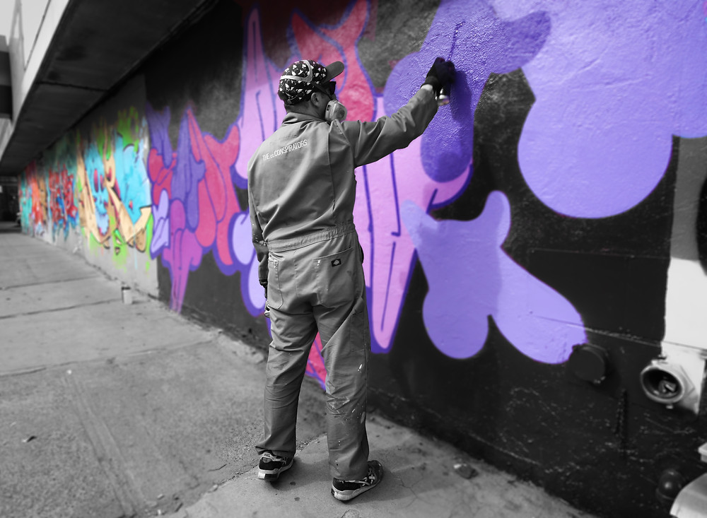 """Adam at work on """"Dream,"""" for JMZ Walls ; photo by Joanna Pan"""