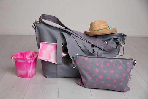 Big bag in grey and neon pink packed as big beach bag for travel with children