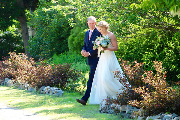 Father escorts his daughter across the lawn at an outdoor wedding in York, Maine