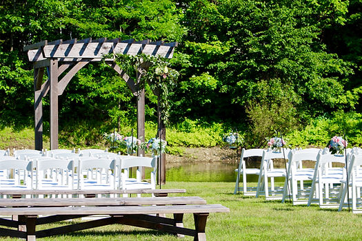 Wedding arch and benches with a pond and fountain in the background at Foster's Clambakes and Catering in York, Maine