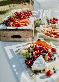 Fruit and cheese displayed on a white tablecloth