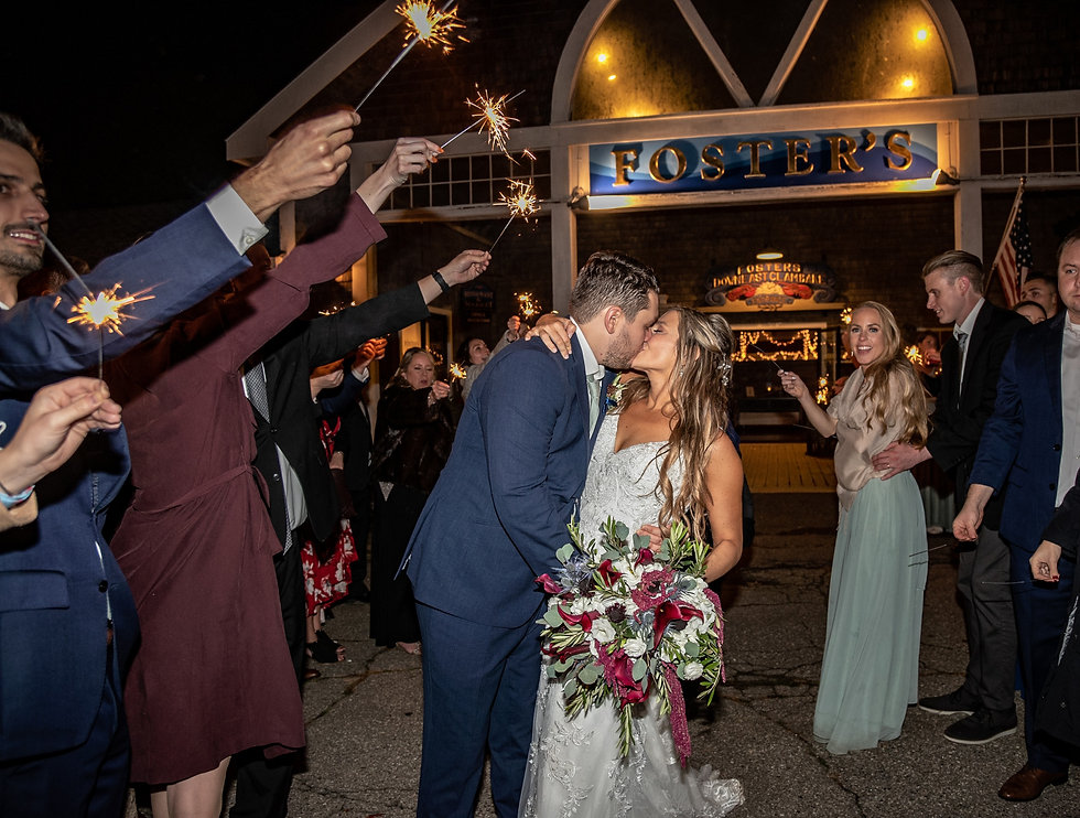 Just married bride and groom kissing in front of Foster's Clambakes and Catering while guests hold sparklers