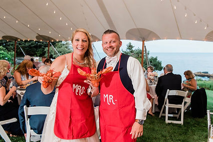 Bride and groom holing lobsters and wearing red Mr and Mrs aprons