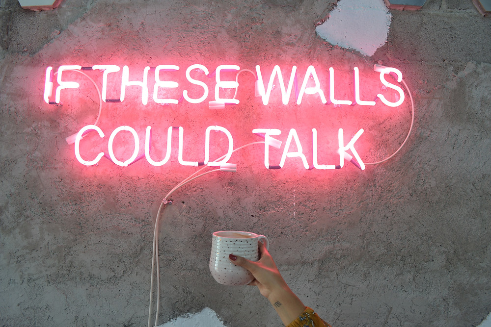 """Neon sign say """"If these walls could talk"""" and hand holding a coffee mug"""