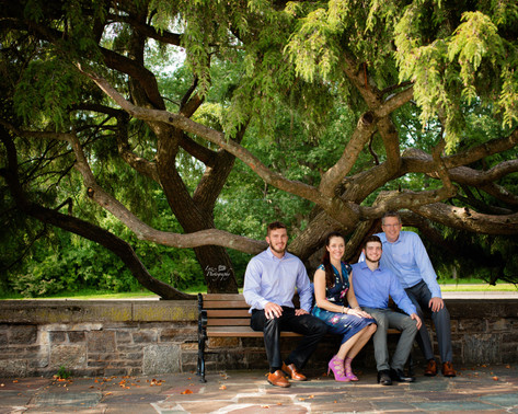 family shoot outside sitting on a bench together