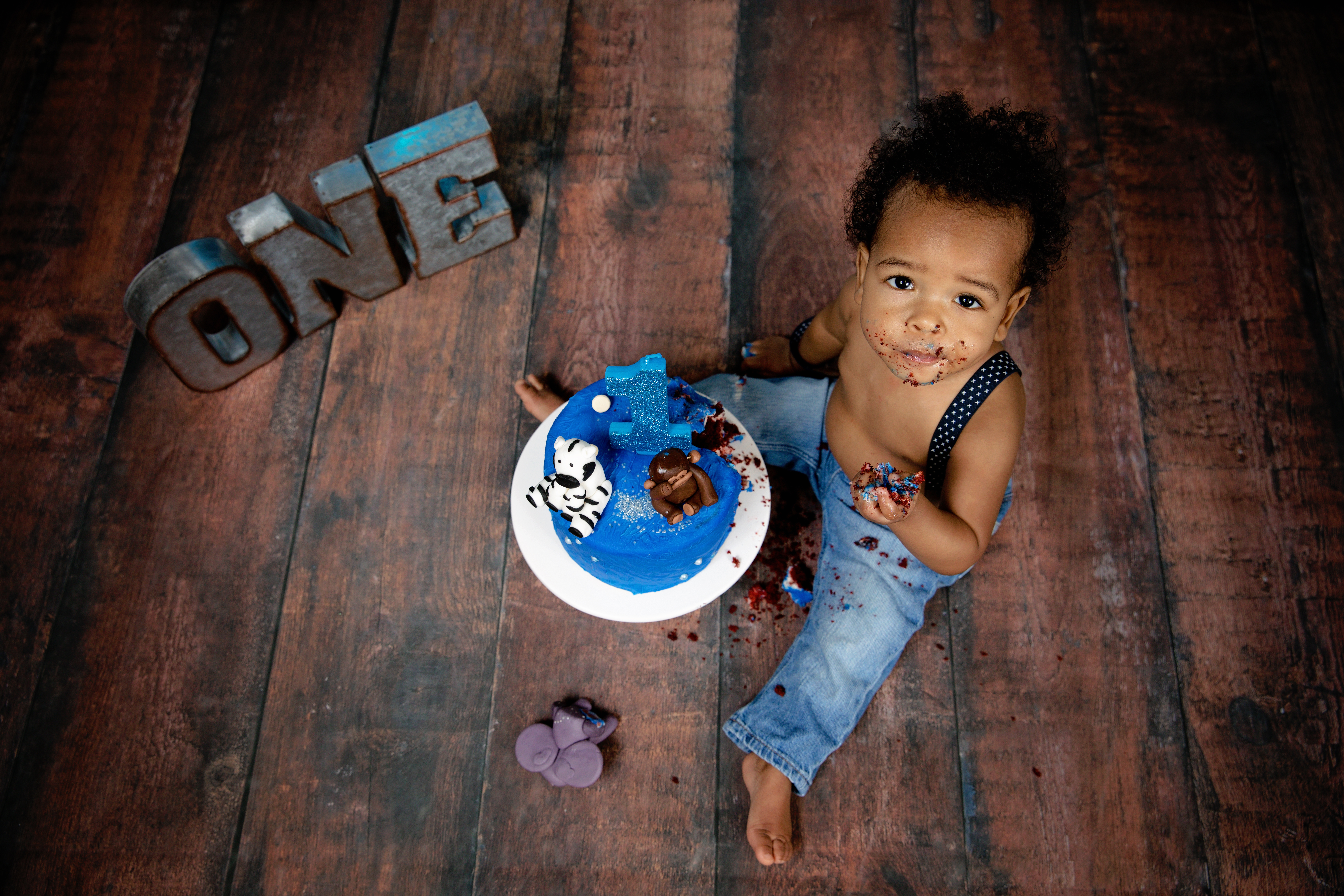 1st birthday blue cake smash in jeans on old wood floor