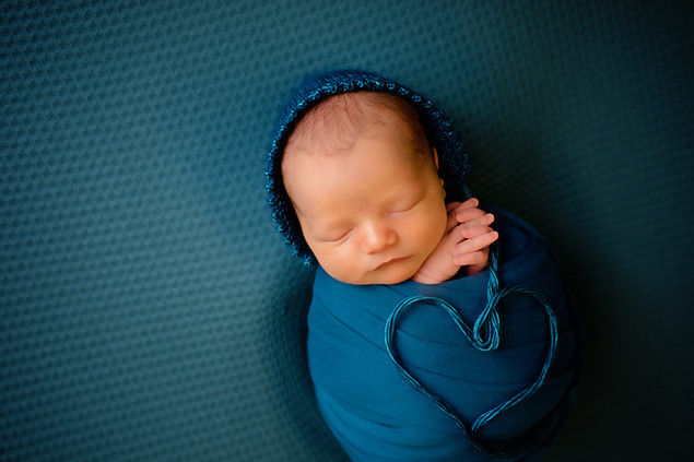 Newborn wrapped with a blue bonnet