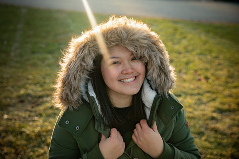 Senior girl in fur trimmed hood with sun behind her during golden hour