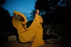 maternity shoot outside wearing a yellow dress