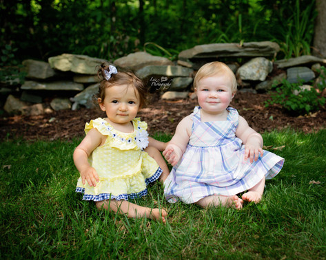 two little girls holding hands sitting in the grass