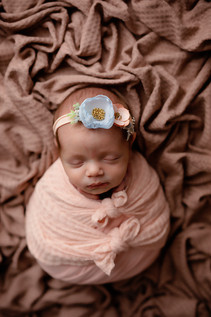Baby girl wrapped with two cute bows around belly and wearing a headband