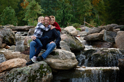family shoot with kids on father sitting on a rock