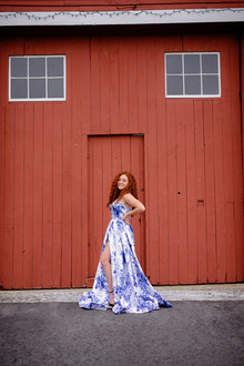 Senior girl with red hair in blue and white dress with her leg out standing in front of a red barn