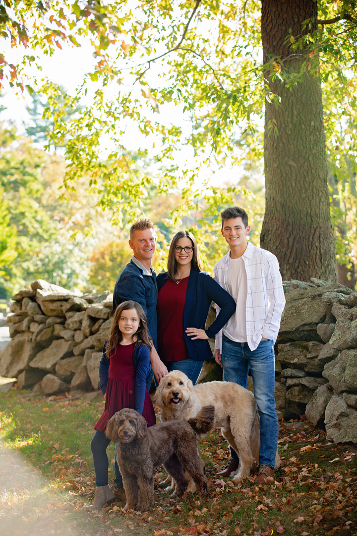 family of 4 with 2 dogs next to a rock wall
