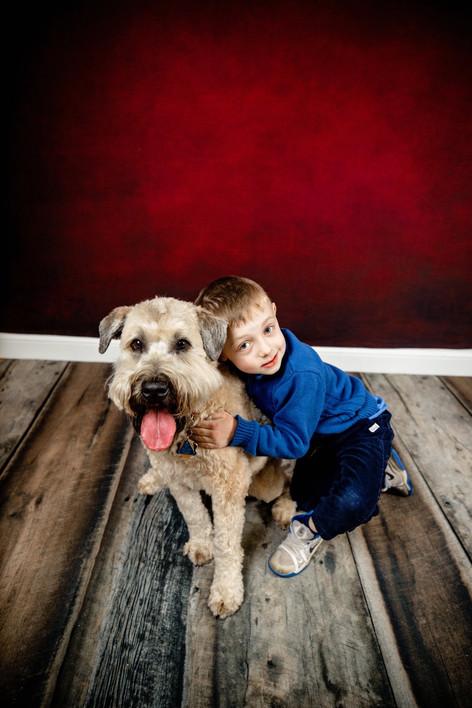 Young boy hugging a wheaten terrier