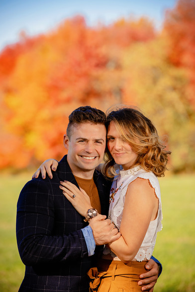 married couple in front of fall foliage