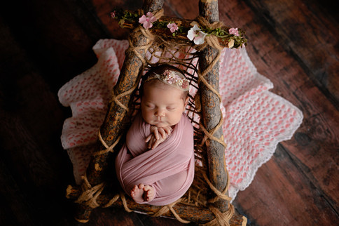 Newborn wrapped in light pink in wooden bed