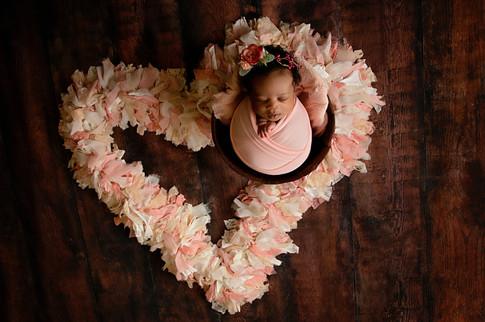 Newborn wrapped in pink in a bucket in a heart shape