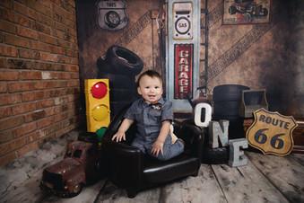 first birthday boy in mechanic suit in a vintage garage scene