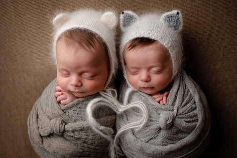 Twins wrapped wearing bear and fox bonette making a heart by their heart